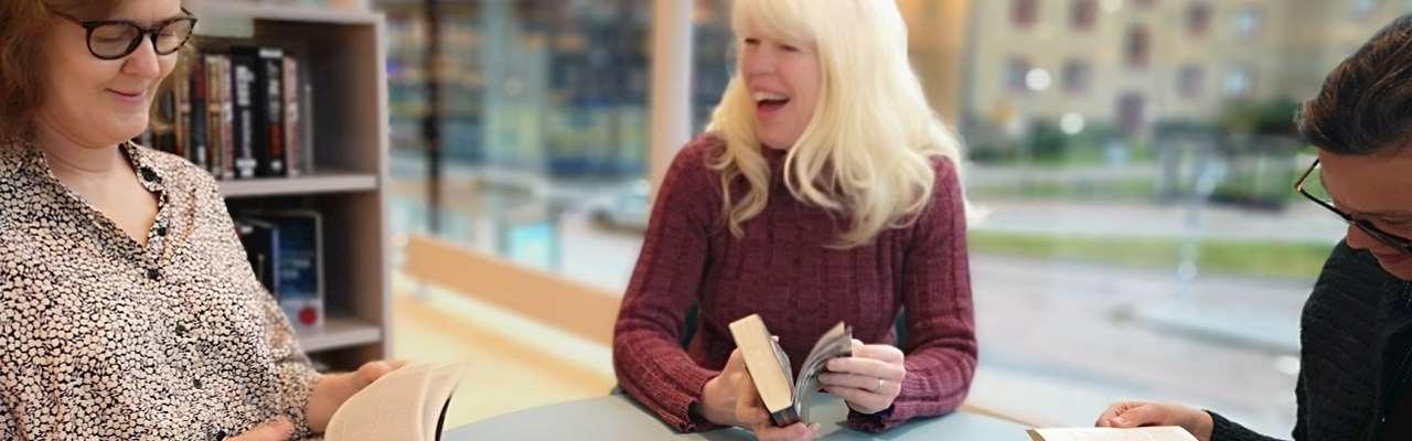 Tre kvinnor läser i böcker