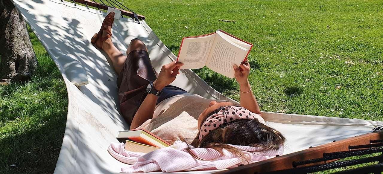 kvinna läser i en hängmatta